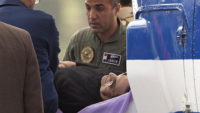 Хосни Мубарак в сопровождении медицинского персонала у здания полицейской академии Каира перед заседанием суда по делу об убийстве демон