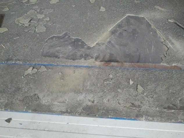 Lose Beschichtung wird von der Ladebrücke bis zu den festen Stellen entfernt