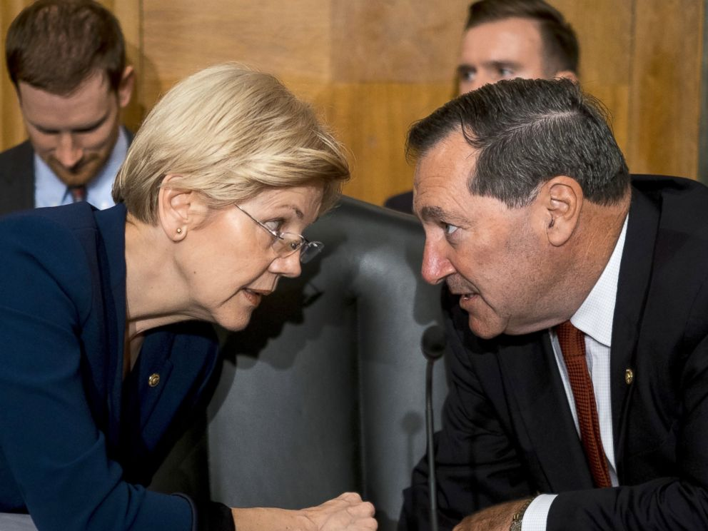 PHOTO: Senator Elizabeth Warren speaks with Senator Joe Donnelly before John Stumpf testifies in front of the Senate Committee on Banking, Housing, and Urban Affairs in Washington, Sept. 20, 2016.
