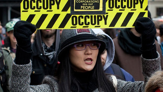 PHOTO: An Occupy Wall Street protester holds a sign during a march towards midtown's Bryant Park Feb. 29, 2012, in New York.