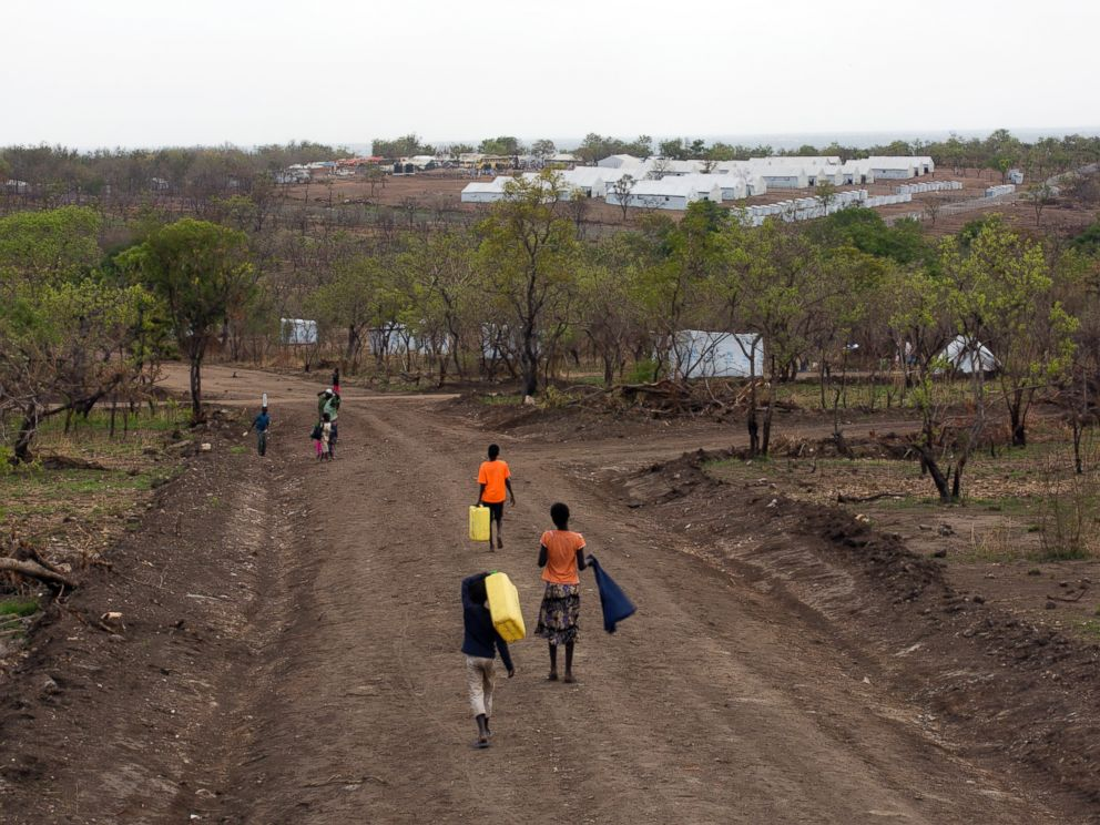 PHOTO: In this Thursday, April 6, 2017 photo, South Sudanese children carry water jugs down a road in the new Imvepi refugee settlement in northern Uganda.