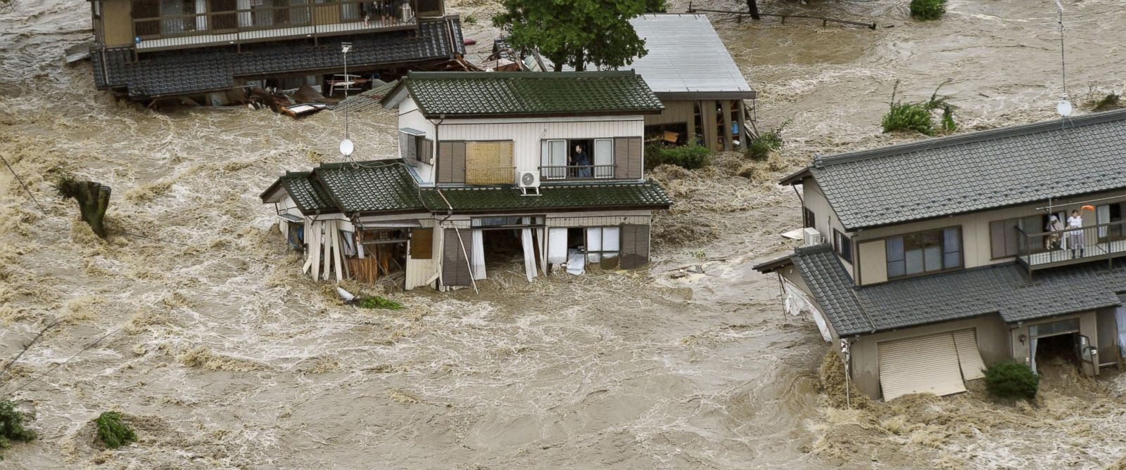 PHOTO: People inside houses wait to be rescued as the houses are submerged in water flooded from a river in Joso, Ibaraki prefecture, northeast of Tokyo Thursday, Sept. 10, 2015.