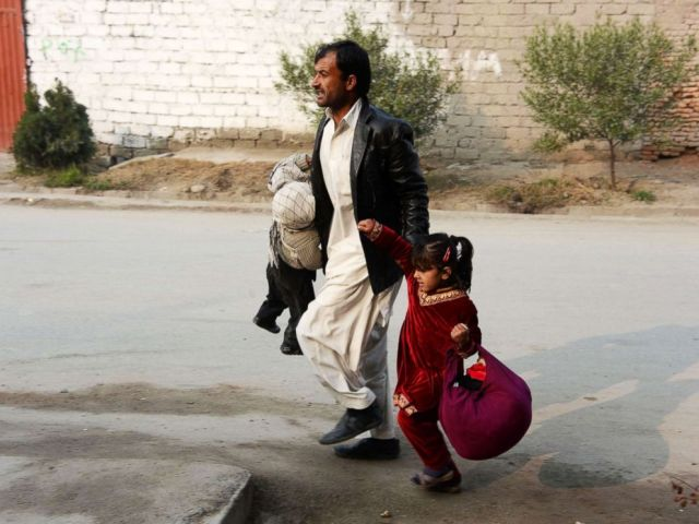 PHOTO: An Afghan man runs with two children near an office of the British charity Save the Children during an attack in Jalalabad, Jan. 24, 2018.