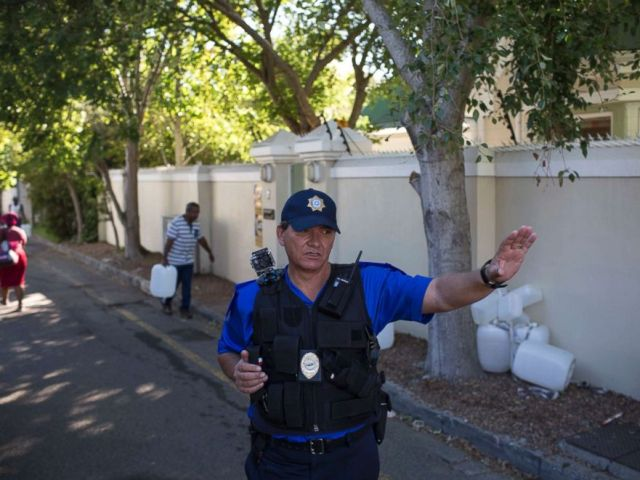 PHOTO: A police officer controls water collection at a source of natural spring water in Cape Town, Feb. 1, 2018.