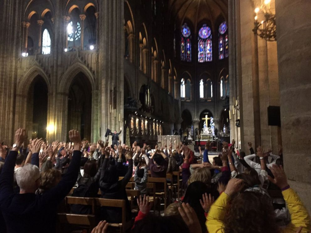 PHOTO: People inside the Notre-Dame Cathedral raise their hands as requested by the police before exiting the church, after a French police shot and injured a man who attacked an officer with a hammer outside the cathedral in Paris, June 6, 2017.