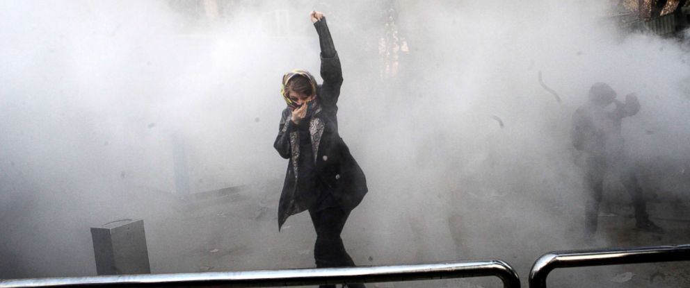 PHOTO: An Iranian woman raises her fist amid the smoke of tear gas at the University of Tehran during a protest driven by anger over economic problems, in the capital Tehran, Dec. 30, 2017.