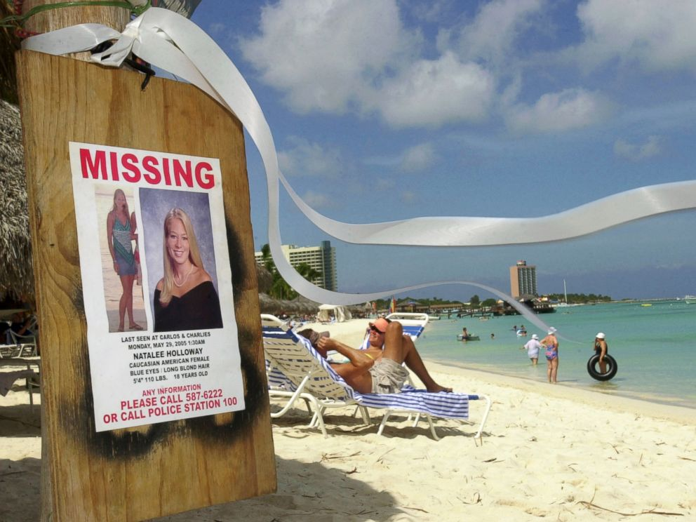 PHOTO: A missing poster for Natalee Holloway, a high school graduate of Mountain Brook, Alabama who disappeared while on a graduation trip to Aruba on May 30, 2005, is seen on Palm Beach where tourists sunbathe in Aruba, June 10, 2005.