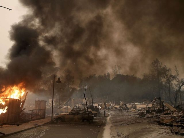 PHOTO: Burned out cars sit next to a building on fire in a fire ravaged neighborhood, Oct. 9, 2017, in Santa Rosa, Calif.