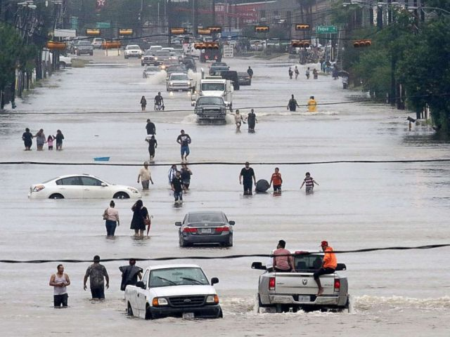 PHOTO: People walk through the flooded waters of Telephone Rd. in Houston, Aug. 27, 2017, as the city battles with tropical storm Harvey and resulting floods.