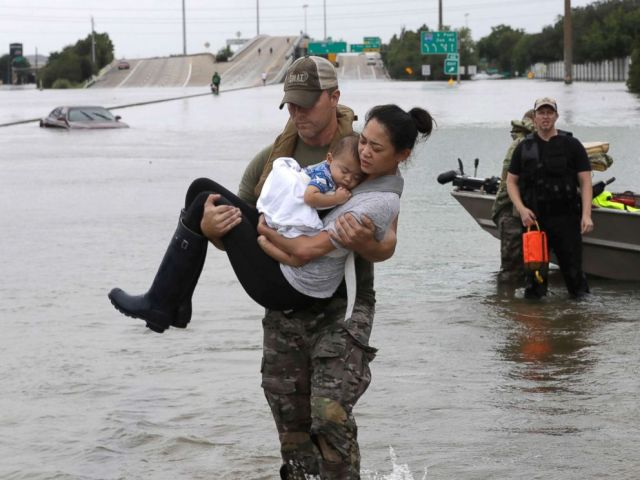 PHOTO: Houston Police SWAT officer Daryl Hudeck carries Catherine Pham and her 13-month-old son Aiden after rescuing them from their home surrounded by floodwaters from Tropical Storm Harvey, Aug. 27, 2017, in Houston.