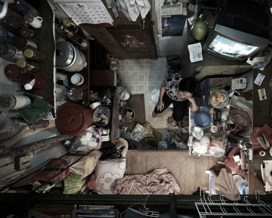 Birds eye view of a tiny house with a woman sitting on the floor. She's surrounded by pots, pans and mess.