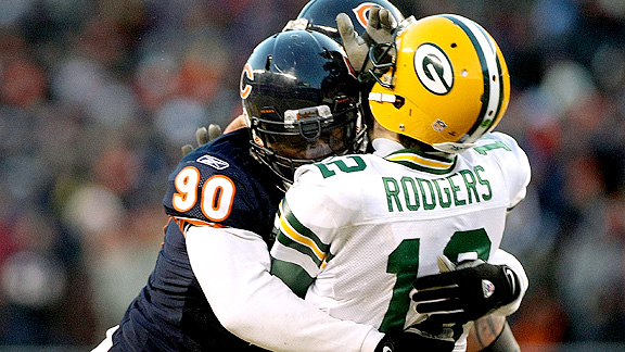 """Bears DE Julius Peppers and Packers QB Aaron Rodgers embrace after learning that they will be teammates in 2014."""