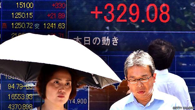 Ciudadanos japoneses frente a una pancarta con indicadores de mercado