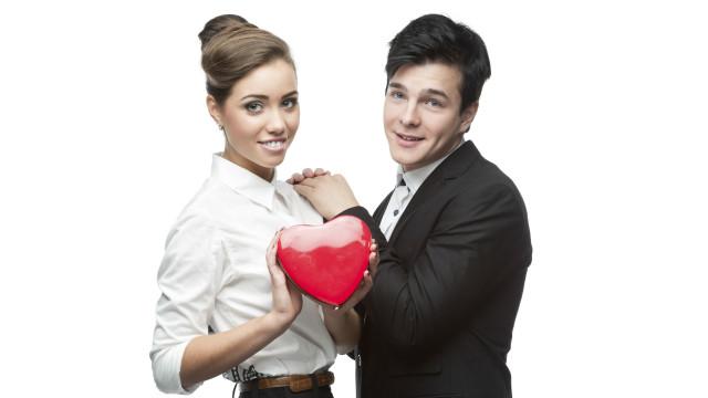 Una pareja sosteniendo un corazón de plástico