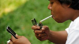 Persona fumando y viendo el teléfono