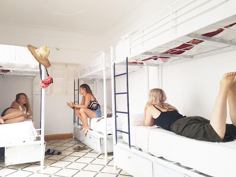3 girls laying in beds in shared dormitory of Majorelle Hostel in Marrakech