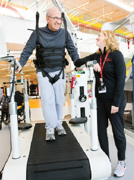 A physical therapist at the Shirley Ryan  AbilityLab leads treadmill training for a patient recovering from stroke. A harness system is used for safety and fall prevention.