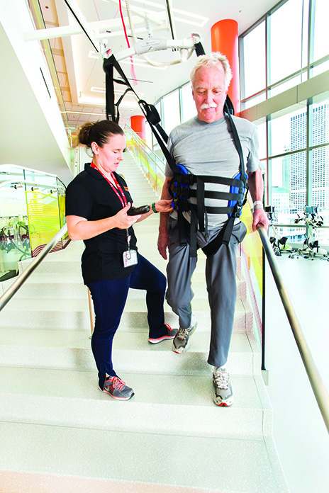 A physical therapist at the Shirley Ryan AbilityLab leads gait training for a patient. The patient's weight is shared with the lift system, which decreases support as the patient's ability increases.