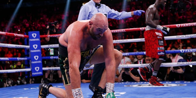 Tyson Fury, of England, gets up after he was knocked down by Deontay Wilder in a heavyweight championship boxing match Saturday, Oct. 9, 2021, in Las Vegas.