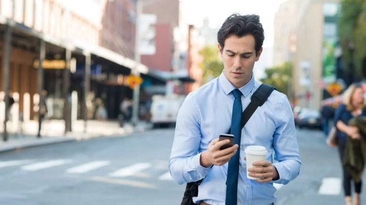 Businessman using smartphone and holding paper cup in an urban scene.