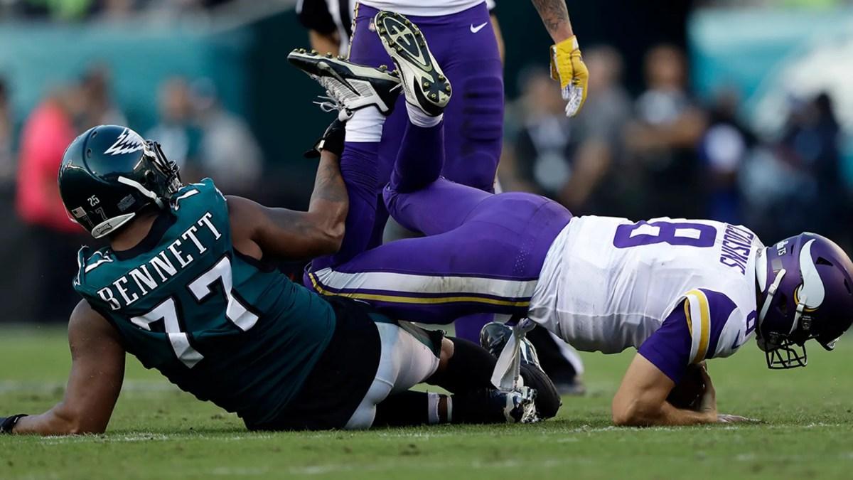 Philadelphia Eagles' Michael Bennett, left, hits Minnesota Vikings' Kirk Cousins during the first half of an NFL football game