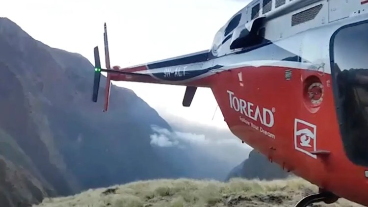 Image from video provided by SIMRIK AIR showing a helicopter that landed close to a storm site after searching for missing mountaineers on the Gurja Himal mountain, in Nepal, Saturday. (SIMRIK AIR via AP)