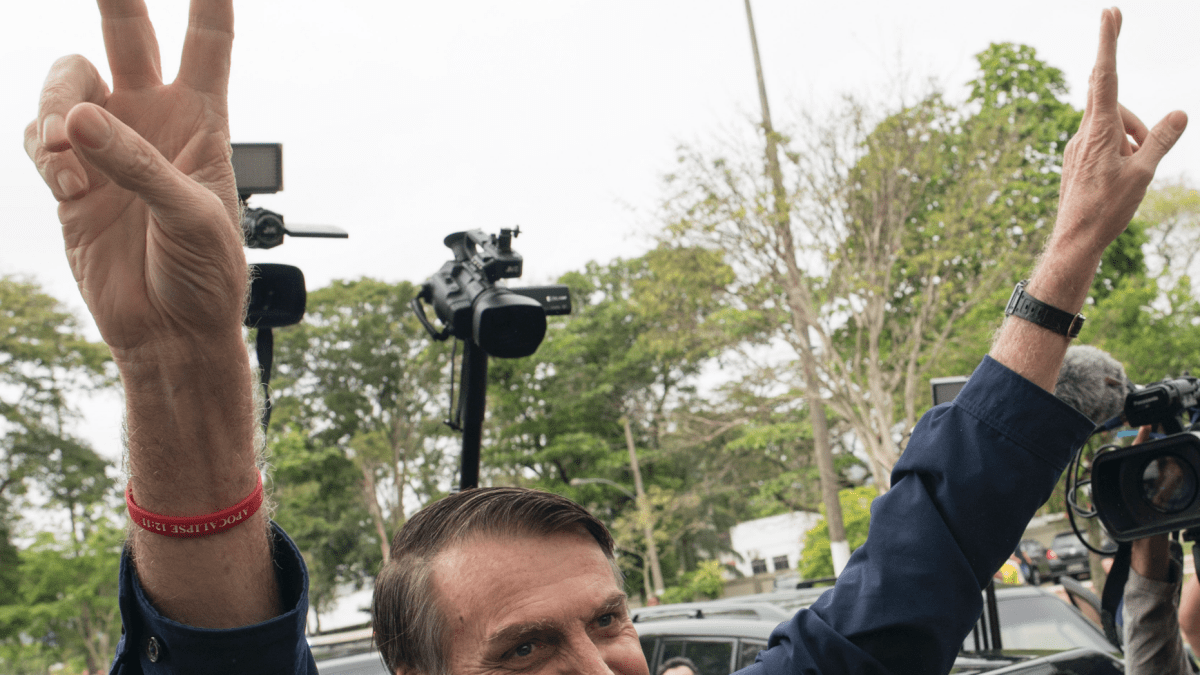 Presidential frontrunner Jair Bolsonaro, of the Social Liberal Party, flashes victory hand signs to supporters after voting at a polling station in Rio de Janeiro, Brazil, Sunday, Oct. 7, 2018. Brazilians choose among 13 candidates for president Sunday in one of the most unpredictable and divisive elections in decades. If no one gets a majority in the first round, the top two candidates will compete in a runoff. (AP Photo/Leo Correa)