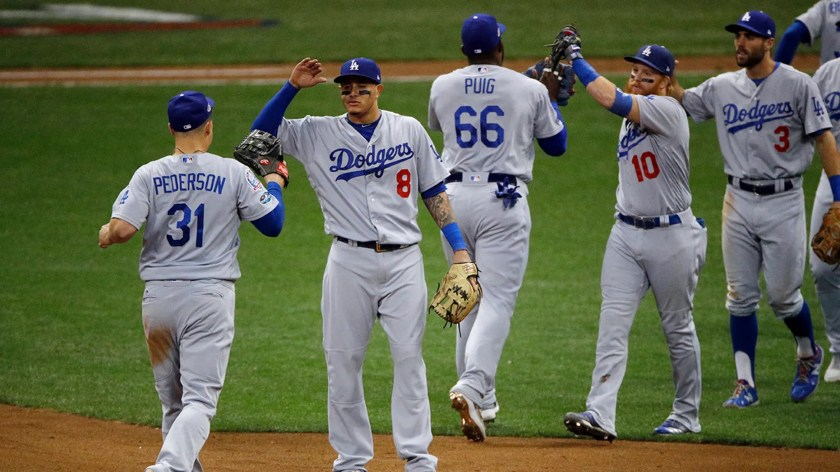 Los Angeles Dodgers players celebrate after Game 2 of the National League Championship Series baseball game against the Milwaukee Brewers Saturday, Oct. 13, 2018, in Milwaukee. The Dodgers won 4-3.