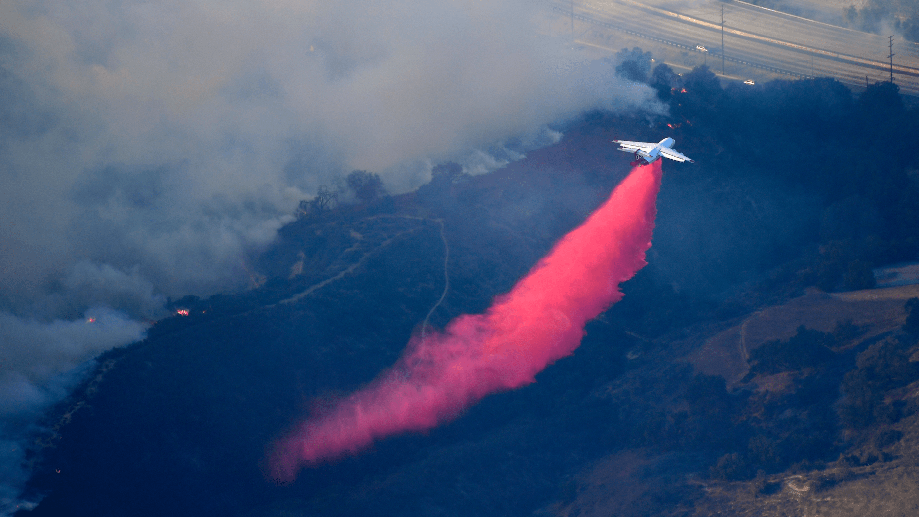 An air tanker drops flame retardant to protect homes as fires burn Friday, Nov. 9, 2018, as seen from a helicopter over the Calabasas section of Los Angeles. Flames driven by powerful winds torched dozens of hillside homes in Southern California, burning parts of tony Calabasas and mansions in Malibu and forcing tens of thousands of people - including some celebrities - to flee as the fire marched across the Santa Monica Mountains toward the sea. The cause of the blazes was not known. (AP Photo/Mark J. Terrill)