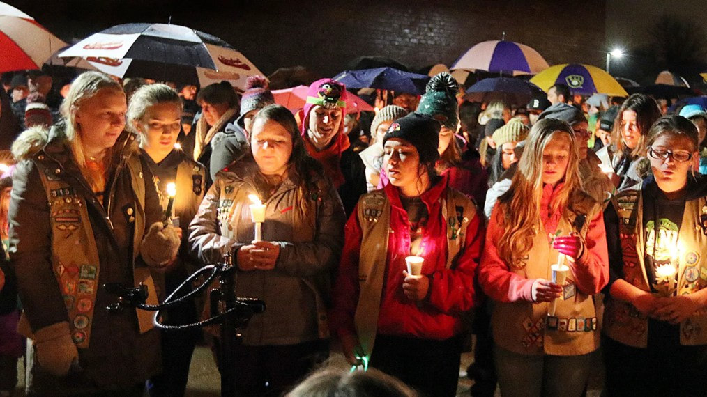 Girl Scouts sing as hundreds of community members turn out in the rain Sunday evening for a candlelight vigil at Halmstad Elementary in Chippewa Falls, Wisconsin.