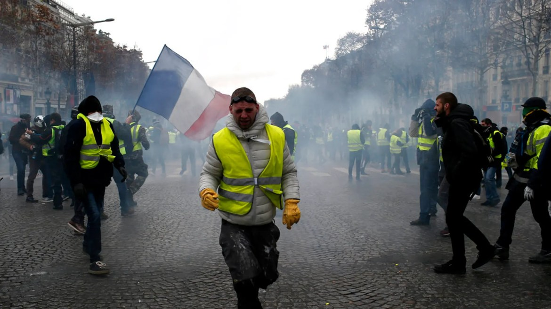 Une manifestante portant un gilet jaune grimace aux gaz lacrymogènes samedi 8 décembre 2018 à Paris. Des foules de manifestants à la culotte jaune en colère contre le président Emmanuel Macron et les taxes élevées en France ont tenté de défiler samedi devant le palais présidentiel, entourés par un nombre exceptionnel de policiers se préparant à des violences après les pires émeutes de Paris depuis des décennies.