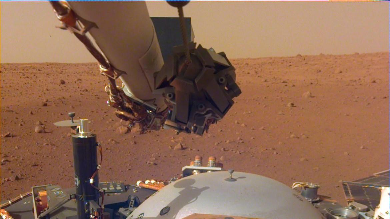 Esta imagen de la cámara de despliegue de instrumentos montada con brazo robótico de InSight muestra los instrumentos en la cubierta de la nave espacial, con la superficie marciana de Elysium Planitia en el fondo. (Crédito: NASA / JPL-Caltech)