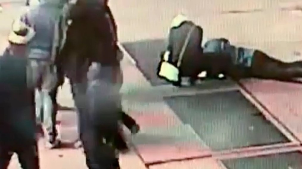 In this Nov. 30, 2018 image taken from surveillance video provided by the New York City Police Department, a man tries to see the engagement ring that he dropped down a utility grate on New York's Times Square. (NYPD via AP)