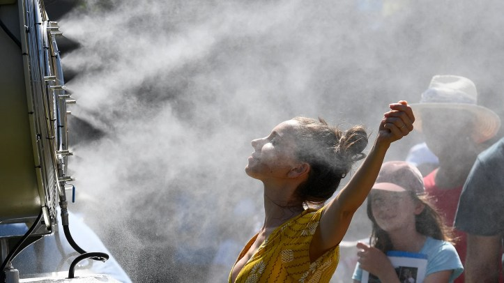 Spectators cool themselves down with a water mist fan during play on day one at the Australian Open tennis championships in Melbourne, Australia, Monday, Jan. 14, 2019.