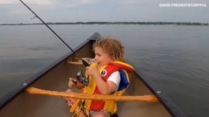Little boy catches the first fish in adorable