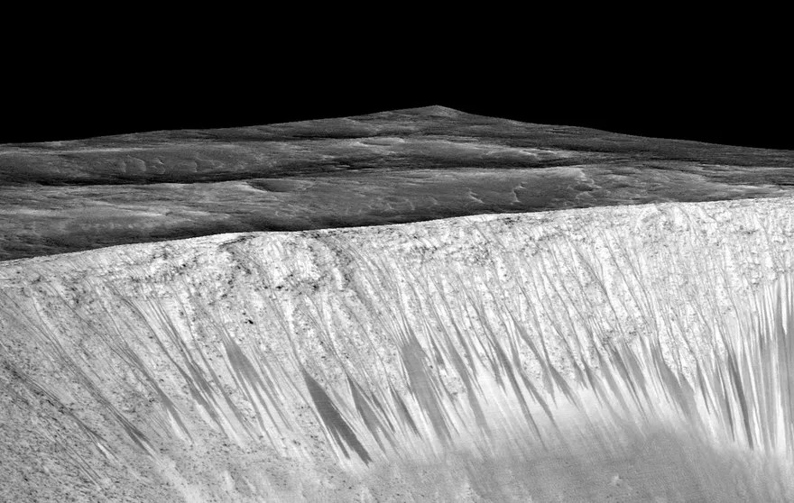 Dark narrow streaks called recurring slope lineae emanating out of the walls of Garni crater on Mars. (Credits: NASA/JPL/University of Arizona)