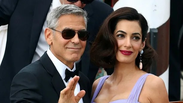 Actor and director George Clooney waves next to his wife Amal as they leave the hotel before the red carpet for the movie Suburbicon at the 74th Venice Film Festival in Venice, Italy September 2, 2017. REUTERS/Alessandro Bianchi - RC1AE9C72100