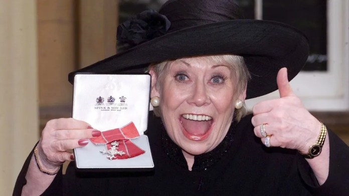 "FILE - This is a Oct. 24, 2000  file photo of British  actress Liz Dawn at Buckingham Palace, London after she received an MBE.  Liz Dawn, the actress who played tart-tongued Vera Duckworth in the long-running British soap opera ""Coronation Street,""  died on Monday Sept. 25, 2017 . She was 77. (Sean Dempsey/PA via AP)"