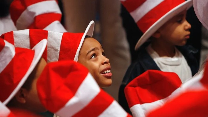 """Children listen to tennis star Serena Williams read Dr. Seuss books to children during """"Read Across America Day"""" to commemorate the 50th birthday of the """"Cat In The Hat"""" character at the New York Public Library in New York, March 2, 2007. Recently, the Dr. Seuss museum in Massachusetts agreed to remove a mural after complaints of racism."""