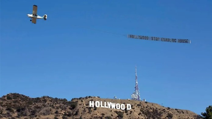Women's advocacy group UltraViolet flies banner over famous Hollywood sign calling for an end to abusein showbusiness.