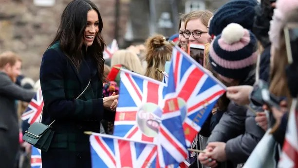 Meghan Markle speaks to wellwishers during a walkabout with Britain's Prince Harry on the esplanade at Edinburgh Castle, Scotland, Tuesday, Feb. 13, 2018. The recently engaged couple are on a one day tour to Edinburgh, and will visit the Castle and observe the firing of the One O'clock Gun. (Andrew Milligan/Pool Photo via AP)