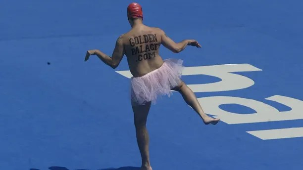 Mark Roberts, a professional streaker from Britain, dances while wearing a tutu during the performances of the synchronised swimming team final at the World Swimming Championships in Barcelona, July 19, 2003.