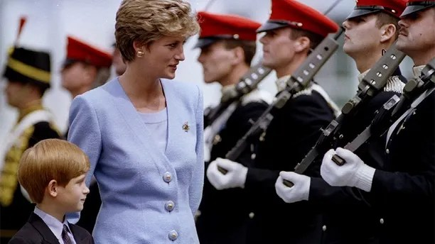 """Princess of Wales, Lady Diana, inspects with her eight-year-old son, Prince Harry, troops at the regiment's base of Bergen-Hohne, July 29. The soldiers of the """"Light Dragoons"""" are an armoured reconnaissance regiment - PBEAHUNJSFR"""