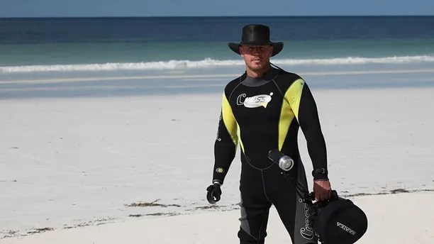 Paul De Gelder stands on the beach with a wet suit and an Aussie hat.