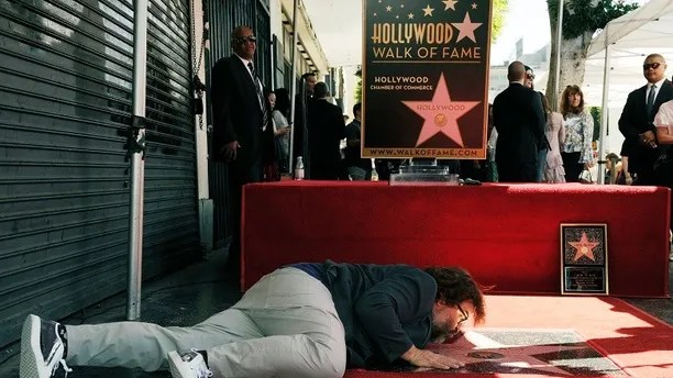 Actor Jack Black lies down to give his new star a kiss during a ceremony on the Hollywood Walk of Fame, Tuesday, Sept. 18, 2018, in Los Angeles. (Photo by Chris Pizzello/Invision/AP)