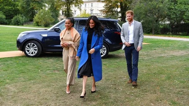 "Meghan, the Duchess of Sussex, centre, accompanied by Britain's Prince Harry, the Duke of Sussex and her mother Doria Ragland walk to attend a reception at Kensington Palace, in London, Thursday Sept. 20, 2018.  Markle was joined by her mother for the launch of a cookbook aimed at raising money for victims of the Grenfell fire. Markle, now the Duchess of Sussex, hosted the reception beside her mother, Doria Ragland, to support the cookbook called ""Together.� (Ben Stansall/Pool Photo via AP)"