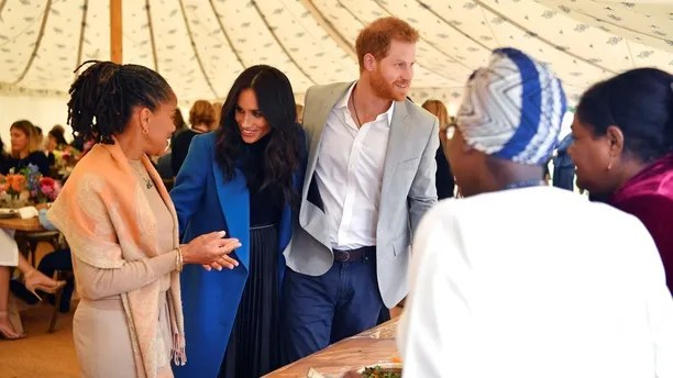 Meghan, the Duchess of Sussex, centre, talks to her mother Doria Ragland, with Prince Harry at centre right, as they attend  a reception for the cookbook
