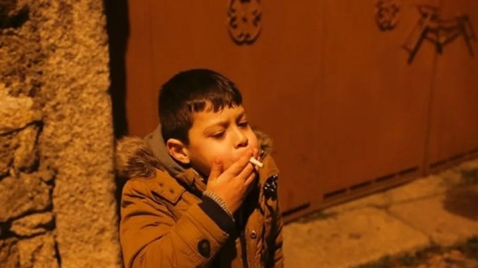 A young boy smokes in the street in the village of Vale de Salgueiro, northern Portugal, during the local Kings' Feast Friday, Jan. 5, 2018.
