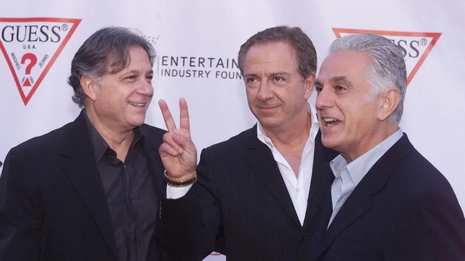 Armand (L) Paul (C) and Maurice Marciano, founders of the GUESS?clothing line pose as they arrive at their company's 20th anniversaryparty in Los Angeles May 9, 2002. The brothers, originally from France,started the company in Los Angeles twenty years ago and sold theirfirst order of 24 pairs of jeans to Bloomingdales. REUTERS/Fred ProuserREUTERSFSP - RTR4YFK