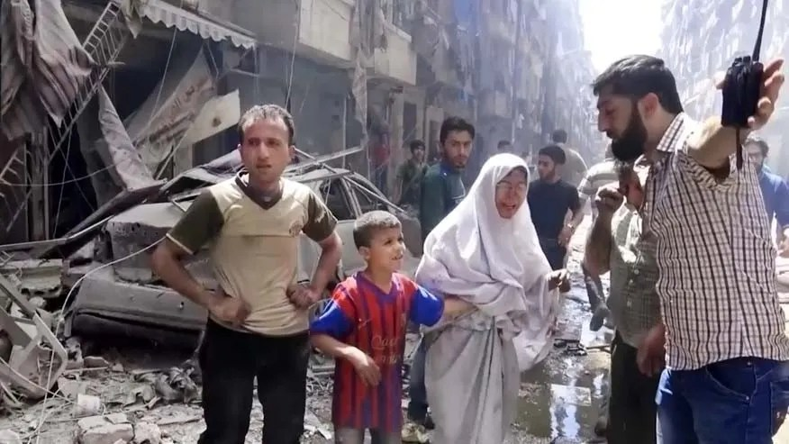 In this image made from video and posted online from Validated UGC, a man leads a woman in tears and child out of the scene after airstrikes hit Aleppo, Syria, Thursday, April 28, 2016.
